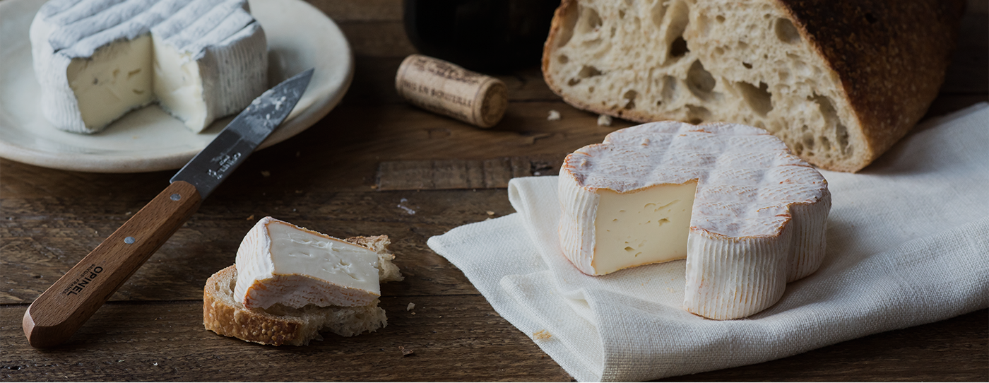 Our Comeback Cow Cheese on a piece of bread. A bread, an opinel knife, a wine cork and our Keep Dreaming cheese.