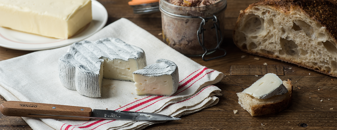 Picture of our Keep Dreaming cheese. On a wood table, with bread, butter, an opinel knife, and pâté.