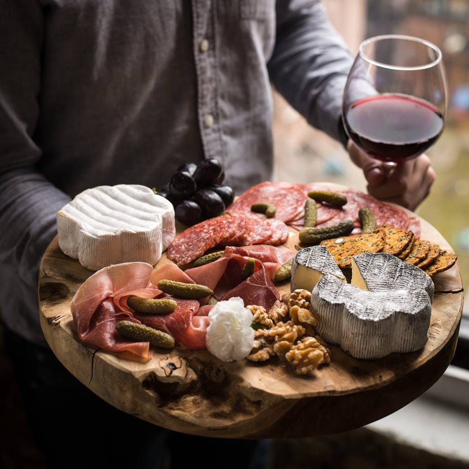 Cheese platter with Keep Dreaming and Comeback Cow cheese, wine, charcuterie, and cornichons.